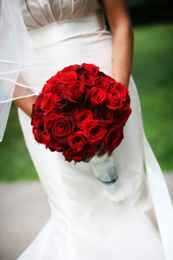 Bridal bouquet of red roses being held by bride