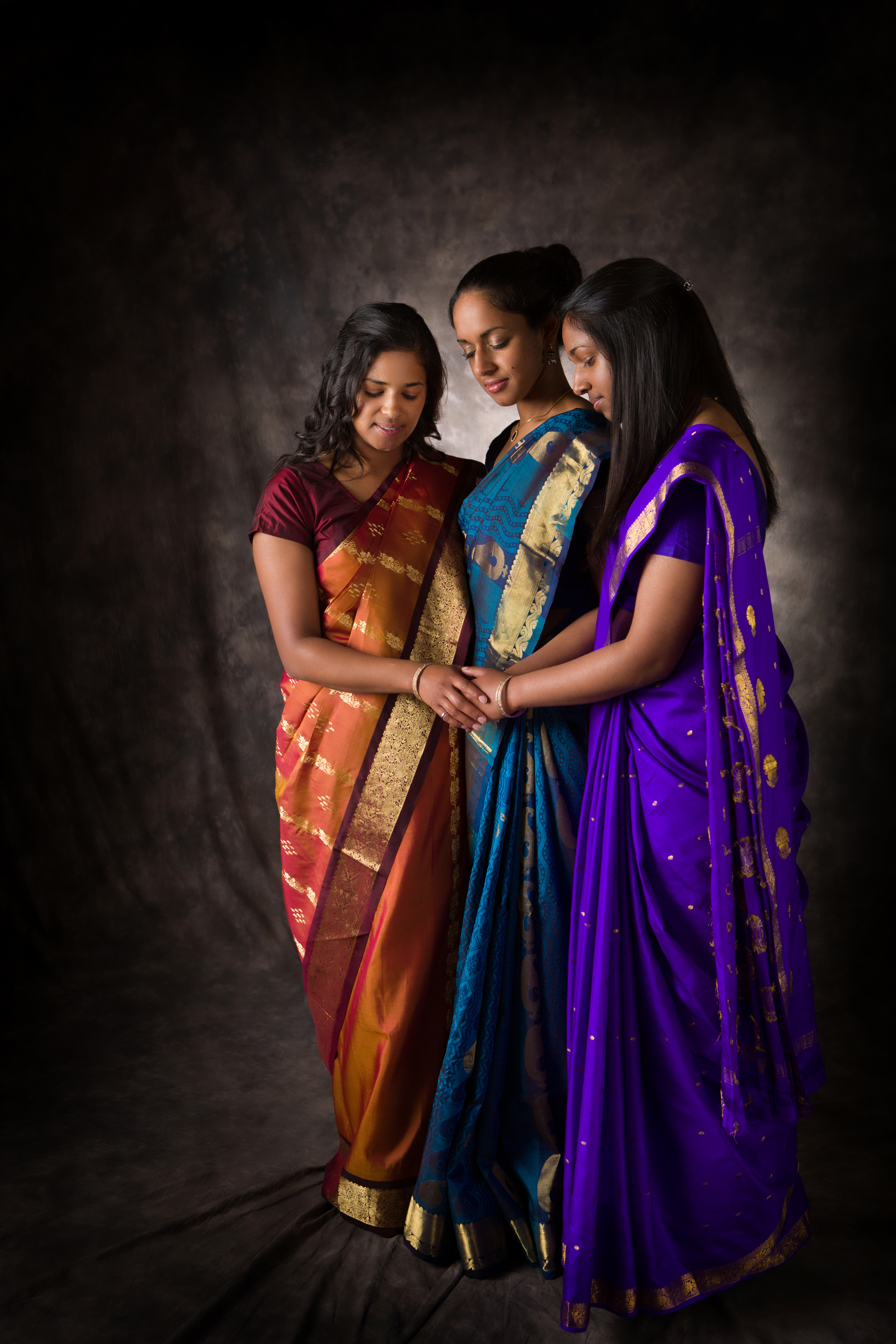 Three women wearing brightly coloured saris standing together