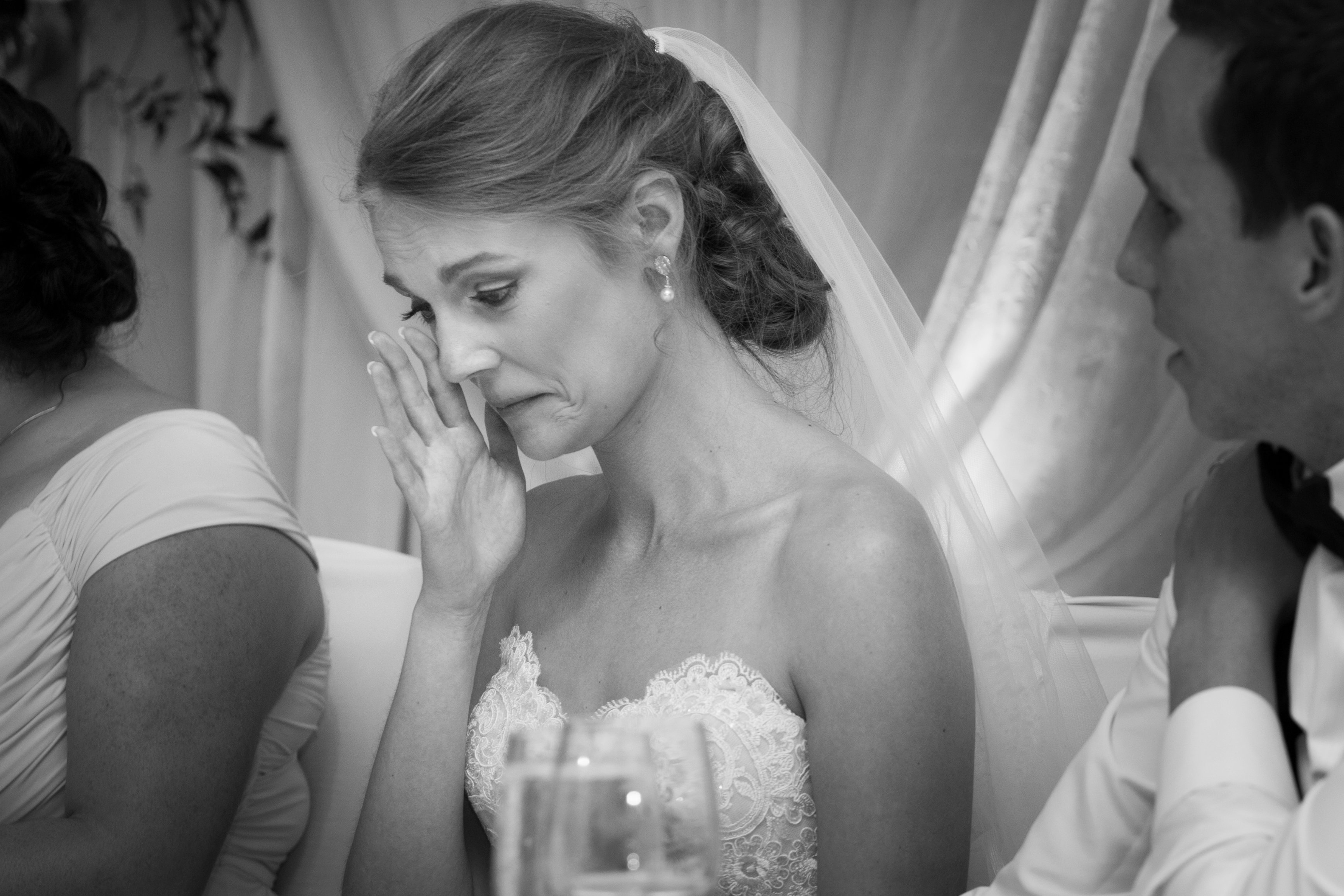 Bride wiping a tear from her eye while listening to speeches at her wedding reception