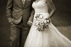 Close up of bride and groom holding hands while bride holds bouquet
