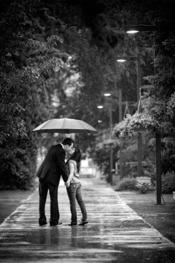 Engaged couple kiss under their umbrella in the rain