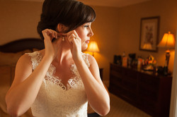 Bride putting on her earrings in a hotel room as she gets ready for her wedding
