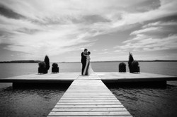 Bride and groom embracing on wooden dock overlooking lake and cloudy sky