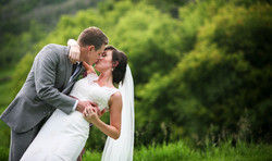 Bride and groom embracing in a romantic kiss