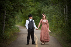Couple dressed in twenties attire pose playfully on a pathway at a park