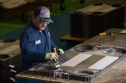 Man in cap and overalls working on heat exchanger part