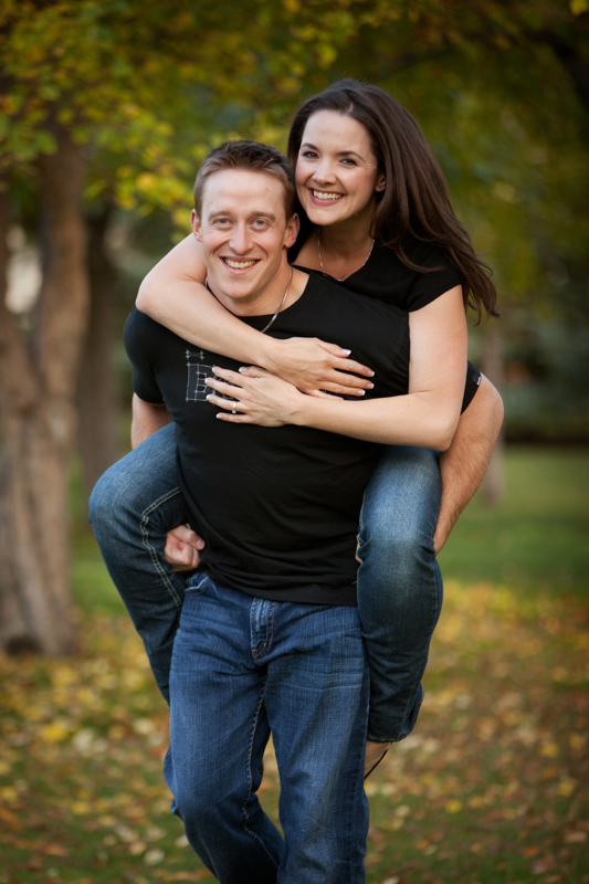 A young man giving his future bride a piggy back ride in a park