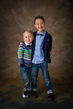 Smartly dressed smiling young brothers with their arms around each other
