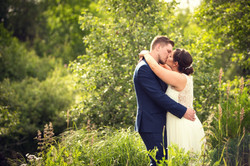 Bride and groom embracing in a romantic kiss with trees in the background