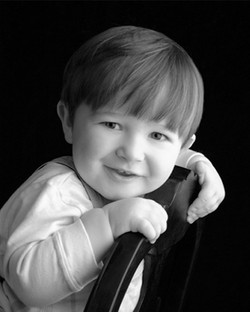 A smiling toddler leaning on the back of a chair smiling
