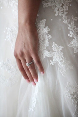 Close up of brides hand wearing diamond engagement ring
