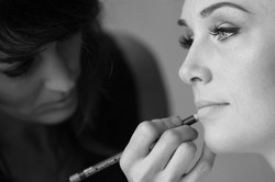 Make up artist applying lipstick to bride