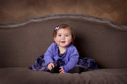Smiling baby dressed in purple sitting on a sofa smiling