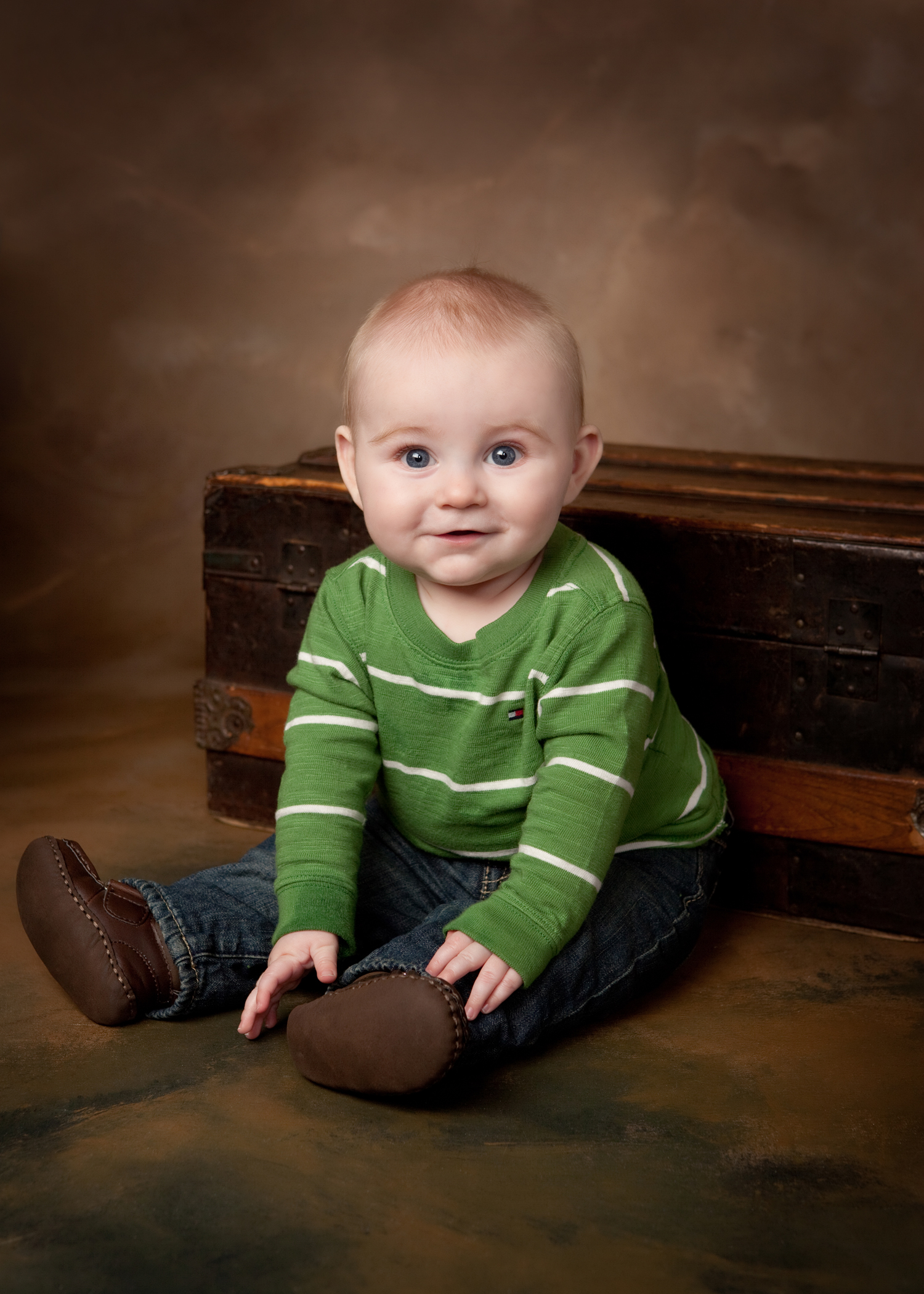 Smiling baby boy in green shirt sitting in front of and old wooden chest