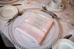 Elegant place setting at reception table with light pink satin napkin and thank you note.