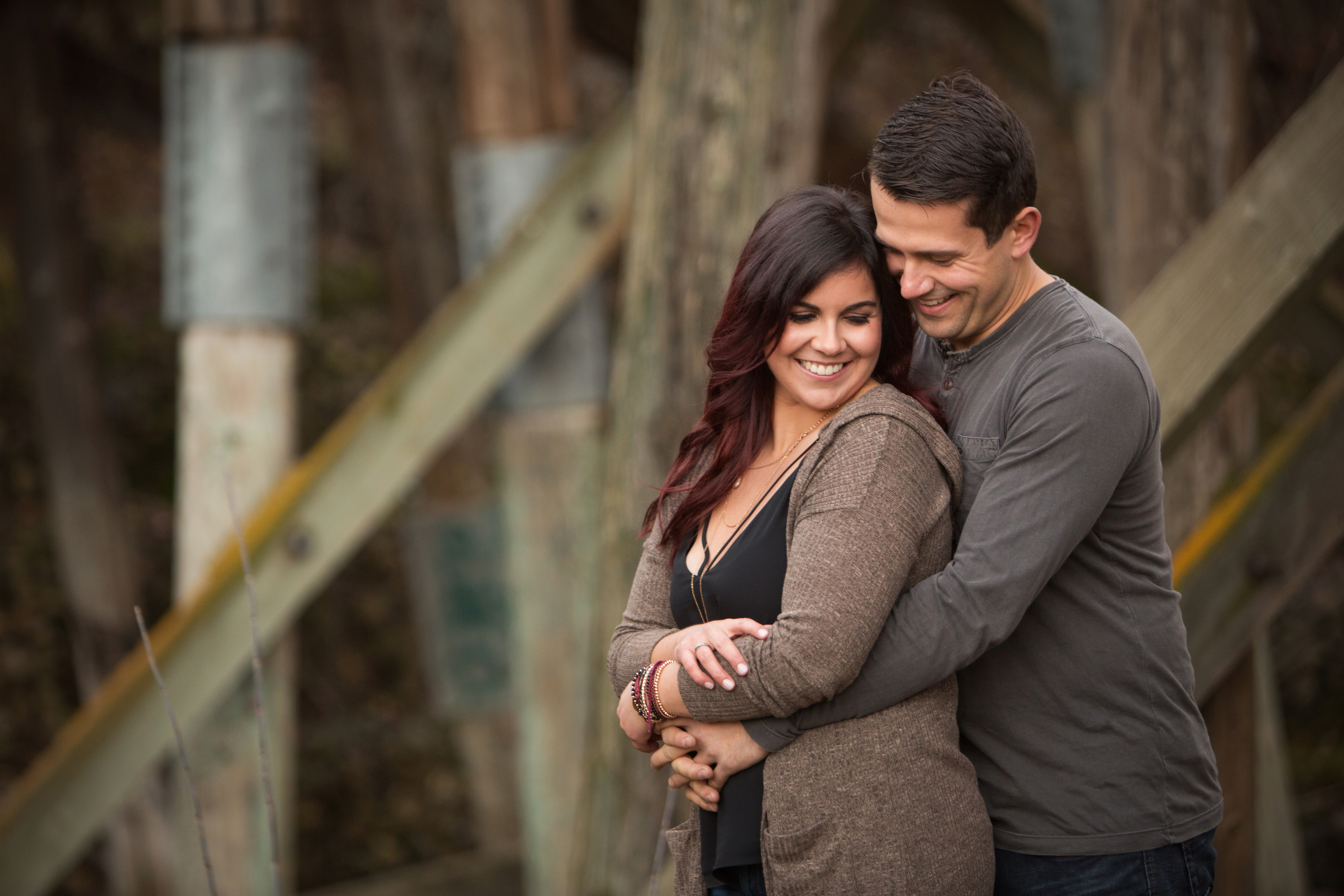 Smiling couple embracing with rustic wood background