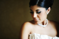 Bride wearing necklace looking down towards her shoulder