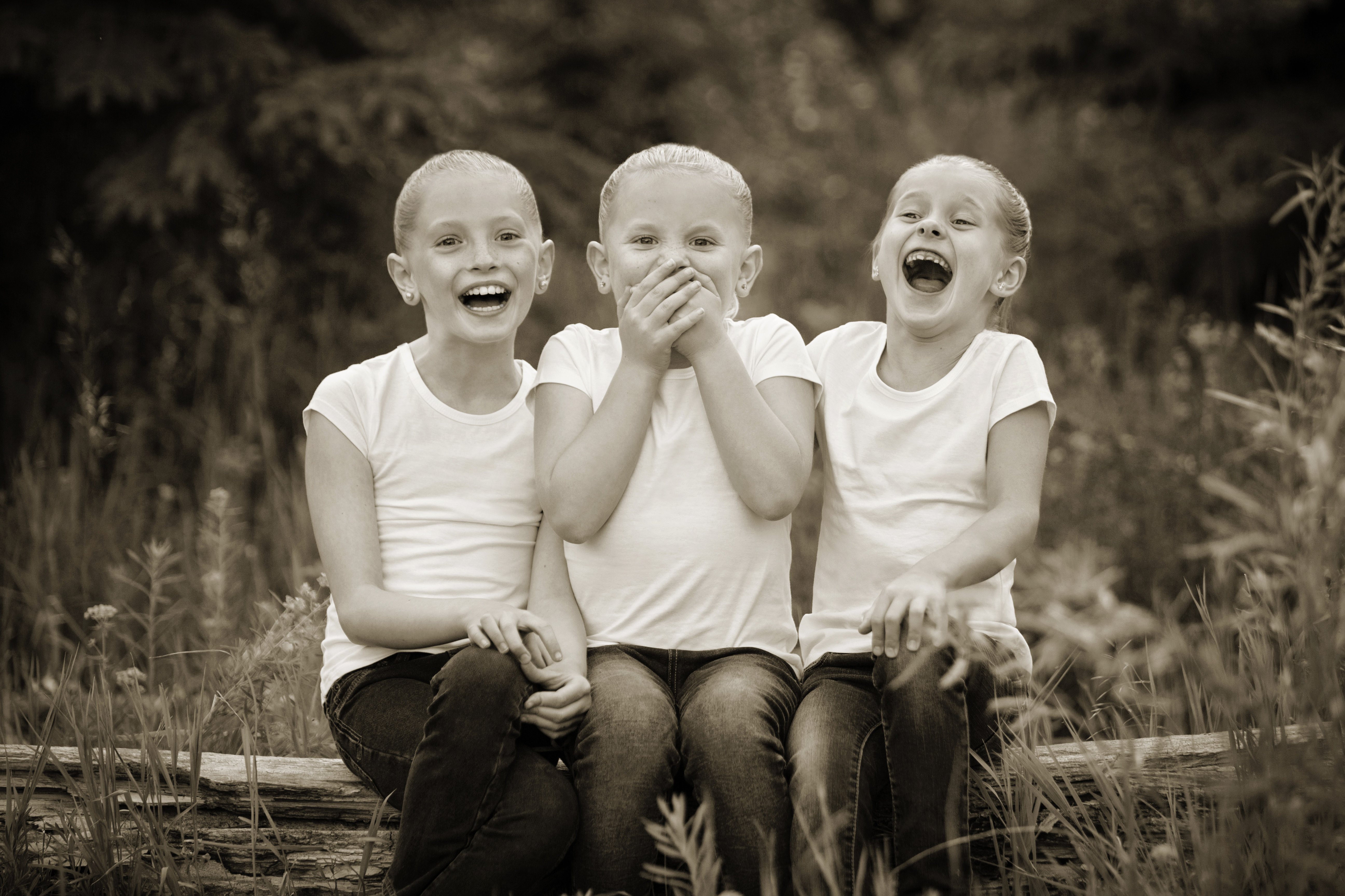Three girls laughing dressed in white shirts