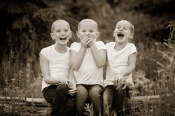 Three girls laughing dressed in white shirts