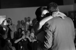 Bride and groom dancing as guests look on
