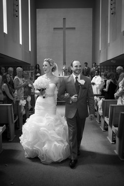 Smiling bride and groom holding hands walking away from church alter as guests look on