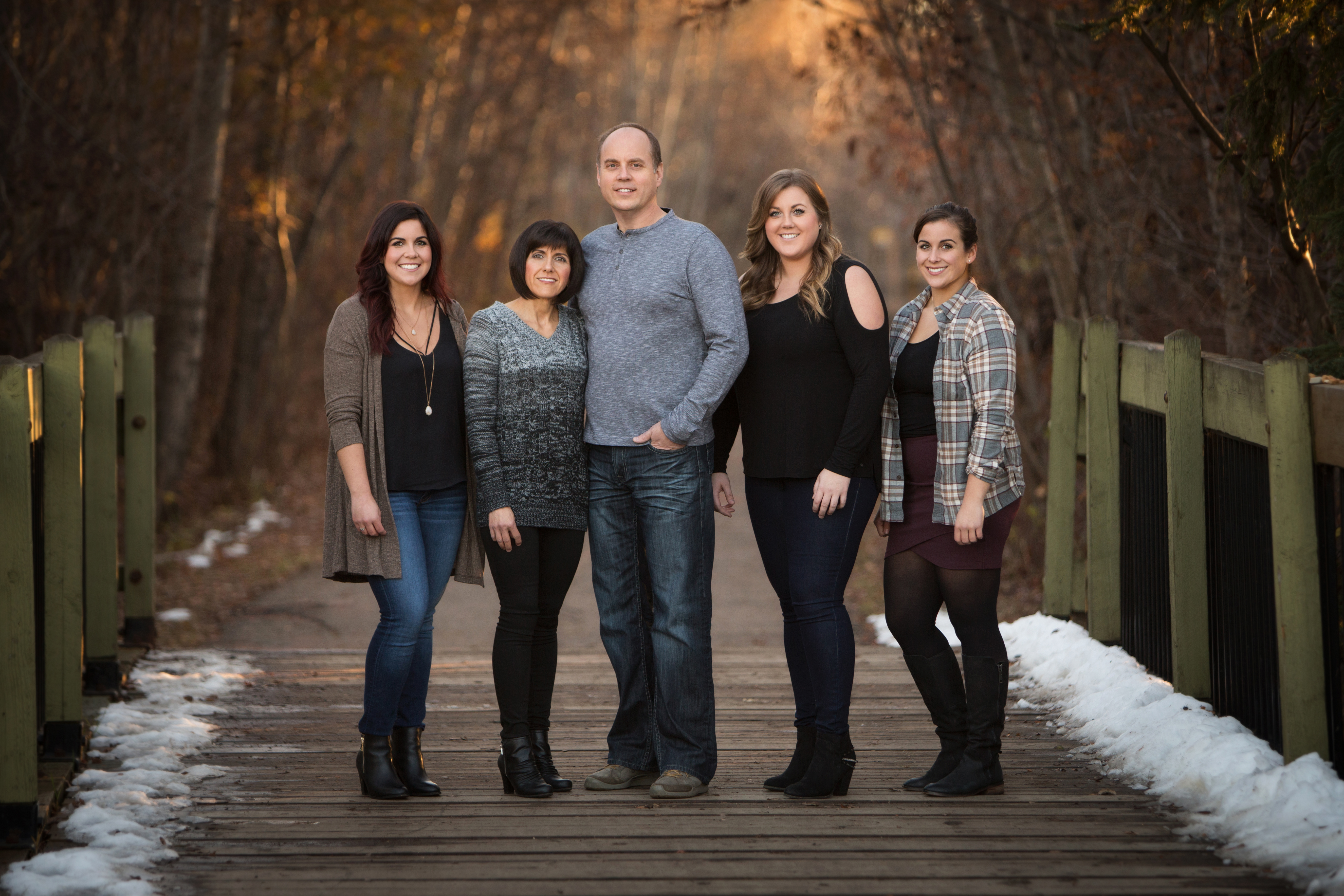 Family of five standing on a pedestrian bridge in Millcreek Ravine