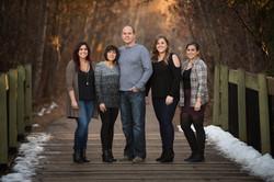 Family of five standing on a pedestrian bridge in Millcreek Ravine