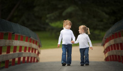 Two young sisters wearing white tops walk hand in hand while walking over a bridge