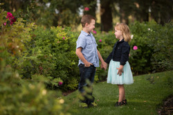 Young brother and sister holding hands looking at each other smiling