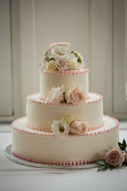 Three tiered wedding cake with pink detailing and flowers