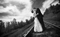 Bride and groom kissing while standing on a train track
