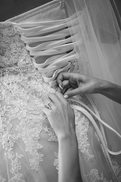 Brides wedding dress being laced up