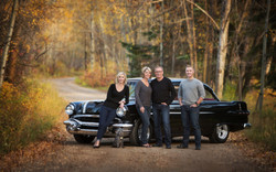 Family of four standing in front of black vintage car