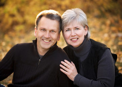 Mature couple stitting together in an outdoor fall setting