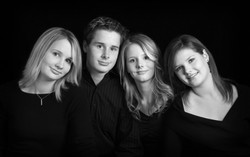 Four young adult siblings dressed in black