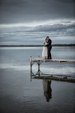 Bride and groom embracing on a dock over looking an Alberta lake with cloudy sky in background