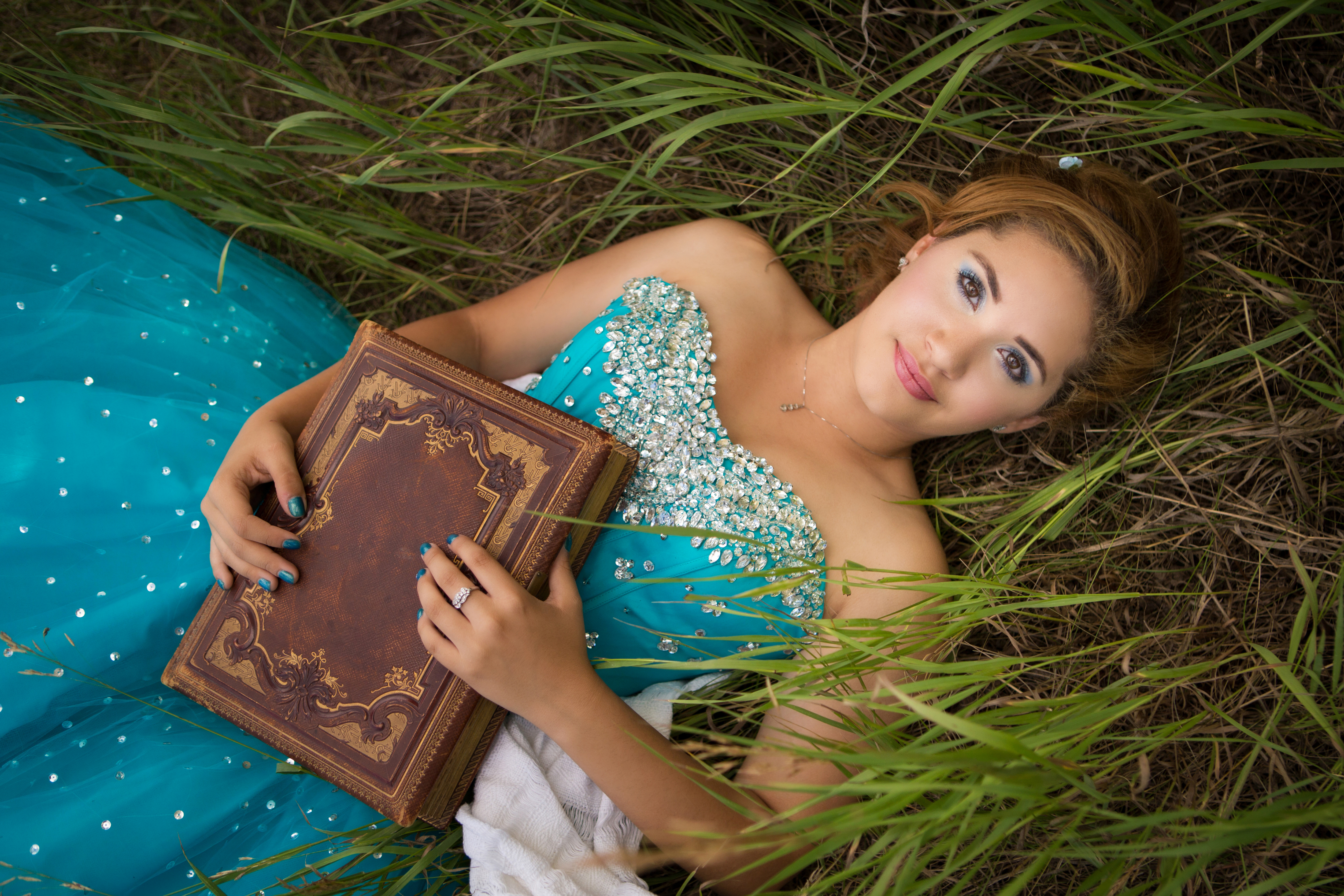 Teen girl in blue sparkly dress laying in grass holding an old book
