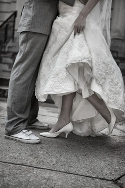 Close up of bride and grooms legs showing their shoes