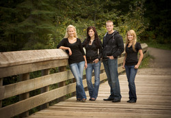 Four young adult siblings standing on a wooden bridge at a park