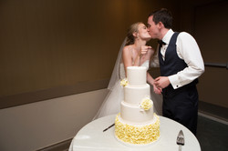 Bride and groom having a kiss while they feed each other cake during the cake cutting ceremony