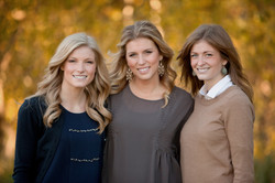 Three young women standing together smiling in an outdoor fall setting