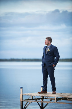 Groom in a blue suit standing on dock looking out onto the lake