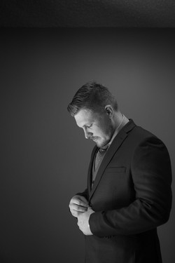 Groom looking down as he buttons up his suit jacket