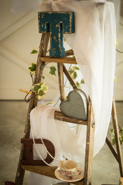 Small vintage ladder holding decorative wedding items