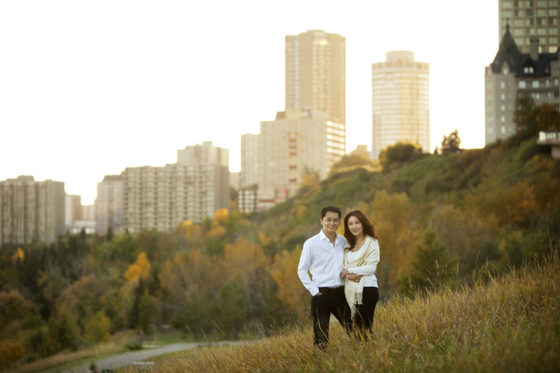 Couple standing in the tall grass with Edmonton skyline in the backgound