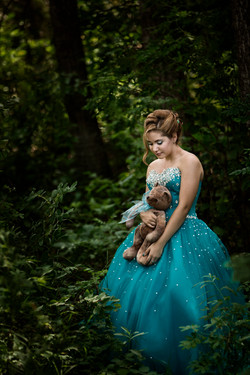 Teen girl in sparkly blue dress standing in the forest holding a teddy bear