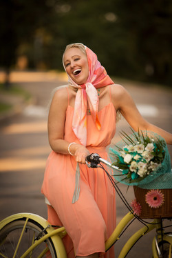 Young woman dressed in orange laughs while sitting on her bike