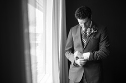 Groom standing near window buttoning up his cuff links
