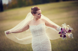 Bride holding out her veil while looking down at her flowers