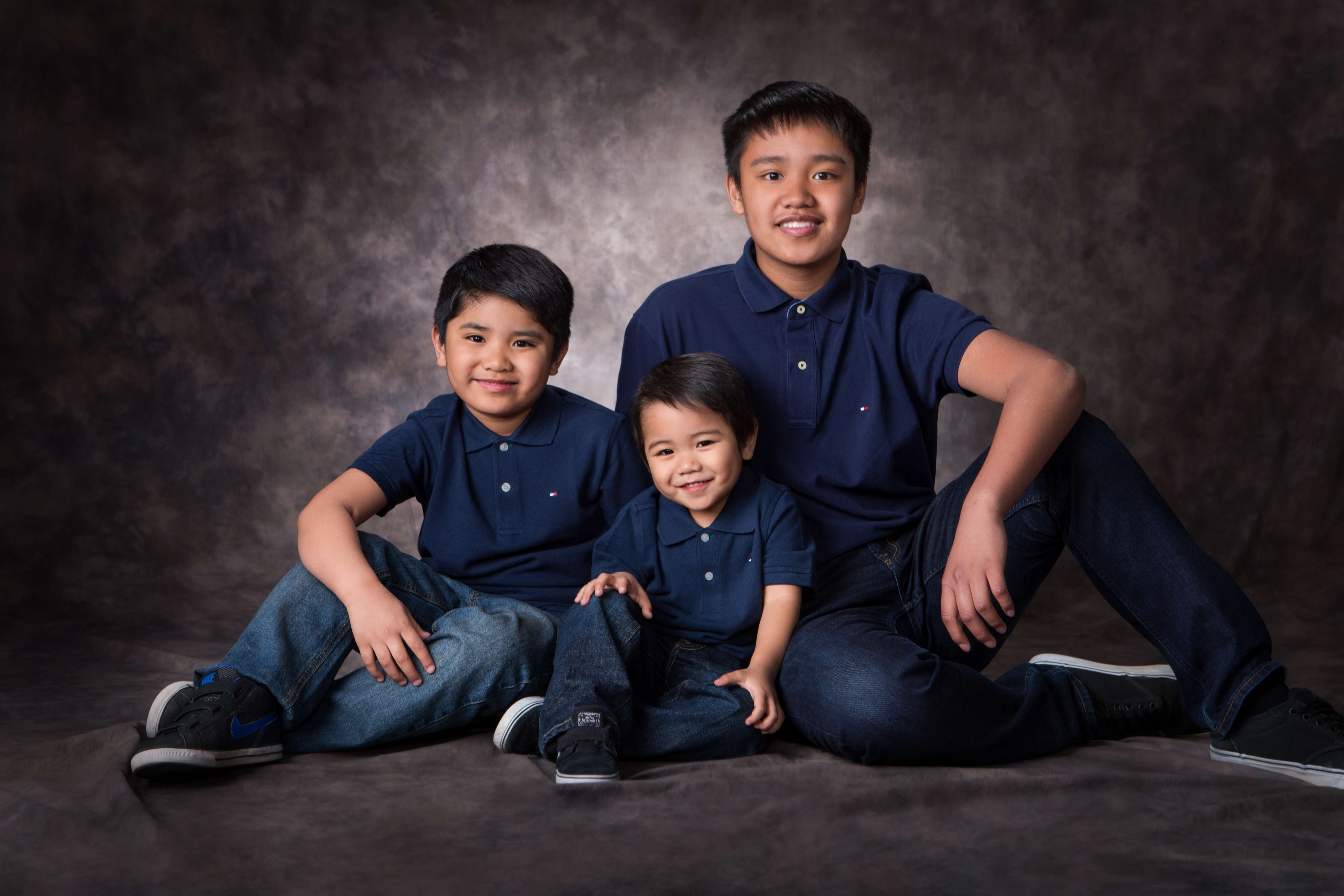 Three sibling boys in blue shirts sitting together